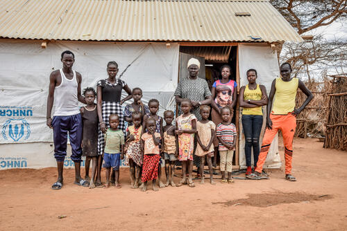 Nyakun Kuok and her family standing outside her house in Dagahaley camp