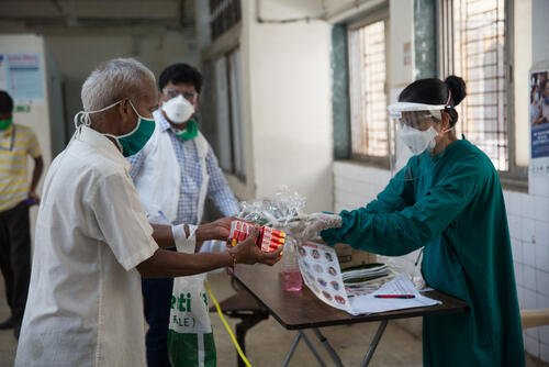 MSF nurse distributing maks and soap in the hospital.jpg
