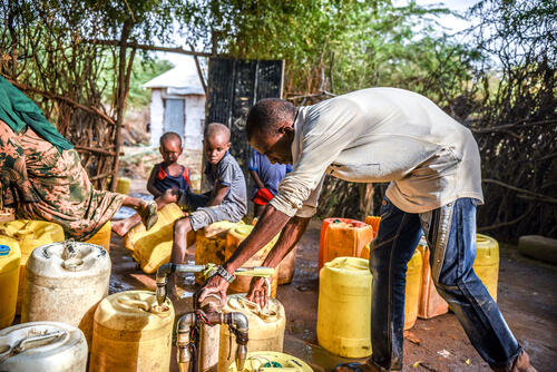 Refugees collecting water at a water point in the camp