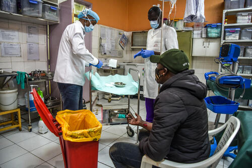 A patient, waits as MSF clinicians prepare to tend to his injuries.
