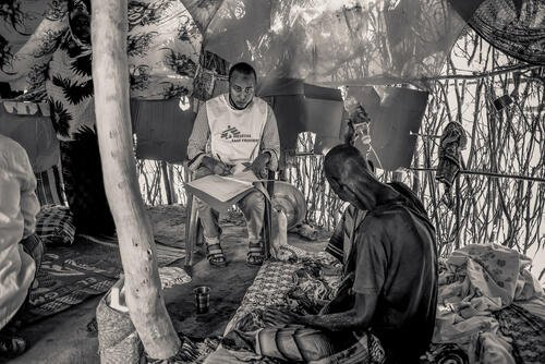 MSF clinician attends to a patient in his house in the camp. The patient is under palliative care.