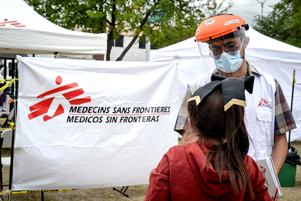 An MSF member is looking at a kid